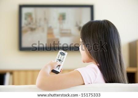 Young girl in living room with flat screen television and remote control - stock photo