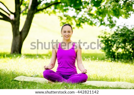 Young girl in lotus pose in the park. girl sitting in the lotus position on grass