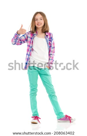 Young girl in lumberjack shirt and green trousers showing thumbs up. Full length studio shot isolated on white. - stock photo