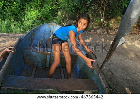 young girl in old boat on sandy beach