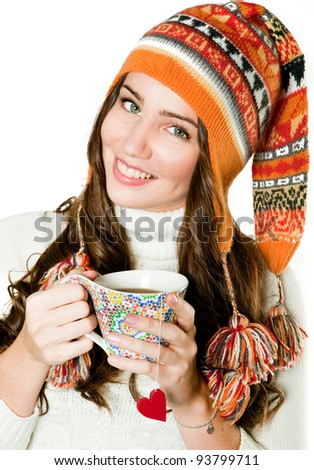 Young girl in orange hood and with cup of hot tea - stock photo