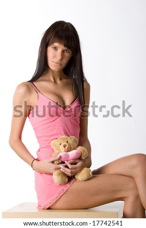 Young girl in pink dress with a toy bear
