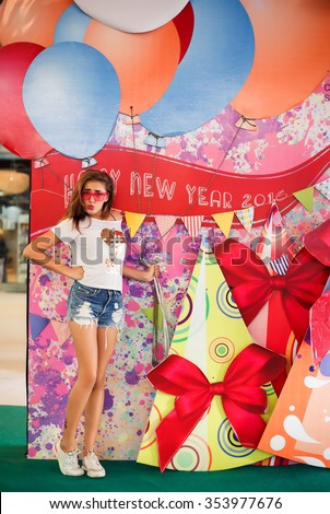 young girl in pink glasses posing next to a Christmas tree decorated with snow bench magic stars and lights at Christmas and the new 2016 vrznotsvetnye balloons gifts and surprises - stock photo