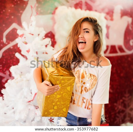 young girl in pink sunglasses posing near decorated Christmas tree in the hands of gifts and surprises, vschastlivoe celebrates Christmas New Year smiles and happiness on his face, the magic - stock photo