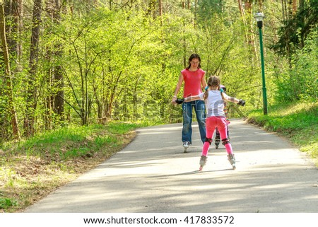 young girl in protective equipment and rollers scating with mother in park, outdoor portrait - stock photo