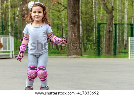 young girl in protective equipment and rollers stands on walkway in park, outdoor portrait - stock photo
