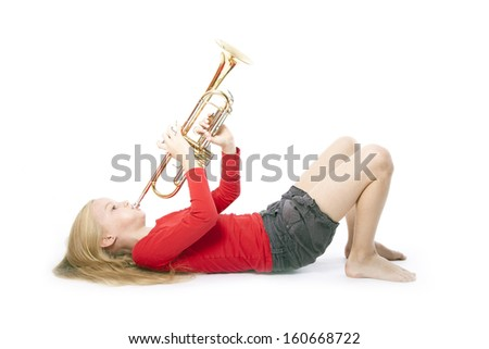 young girl in red playing trumpet laying down against white background - stock photo