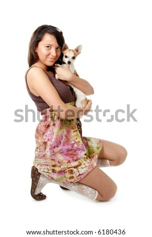 Young girl in skirt and ballet slippers holding chihuahua - stock photo