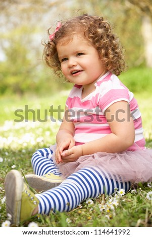 Young Girl In Summer Dress Sitting In Field
