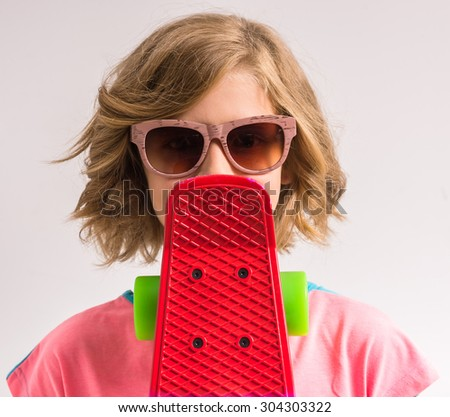 Young girl in sunglasses covering her mouth skateboard in studio against white background. - stock photo