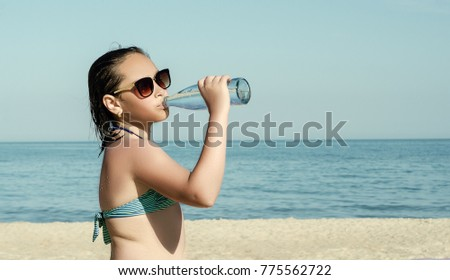 Young girl in sunglasses drinking water while standing on beach at the ocean.