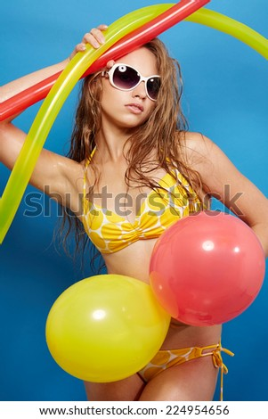 Young girl in swimsuit with balloons on blue background