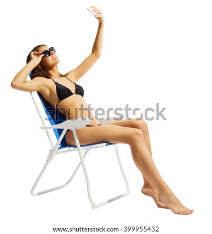 Young girl in swimsuite on chair with mobile phone isolated - stock photo