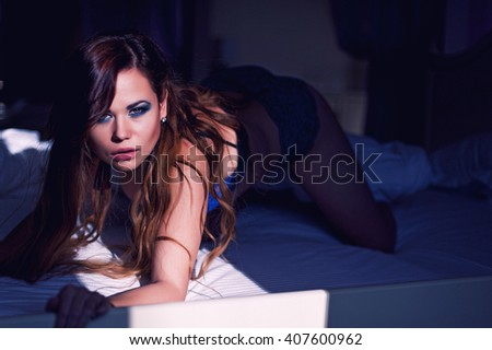 young girl in the early morning luxuriating in bed in the morning summer sun. dressed in blue underwear, a light beam is on it. Luxuriously her healthy long hair a bit disheveled. - stock photo