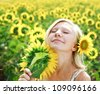 Young girl in the field of sunflowers enjoy a summer day - stock photo