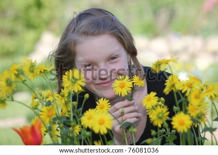 Young girl in the garden with flowers - stock photo