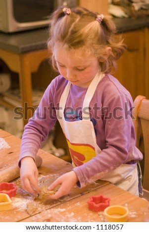 Young girl in the kitchen baking biscuits / cookies. - stock photo