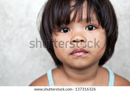 Young girl in the Philippines living in poverty against off-white wall - stock photo