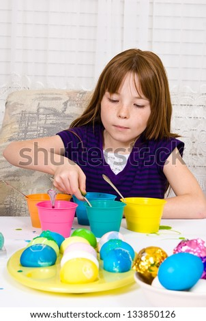 Young girl in the process of coloring Easter Eggs - Step five, the egg completely submerged in the cup of dye