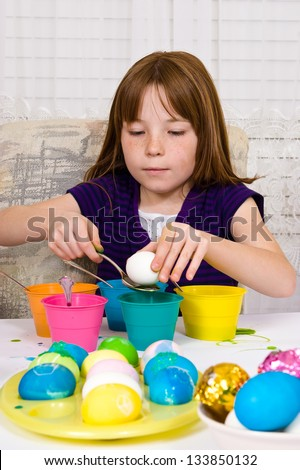 Young girl in the process of coloring Easter Eggs - Step one, placing the egg on a spoon