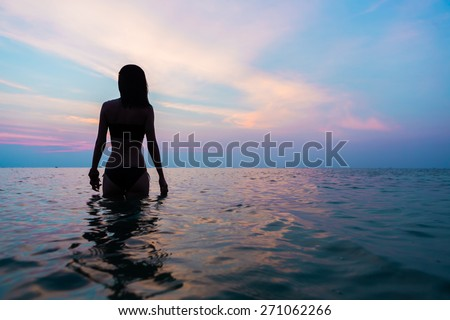 Young girl  in warm water at sunset. Gorgeous colors in the sky and the sea. Perfect shapes reflected in water - stock photo