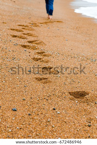Young girl in wet jeans walks down the beach leaving track in orange sand. Low angle, vertical view. Selective focus.
