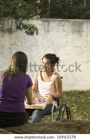Young girl in wheelchair playing cards in with another girl. Vertically framed photo. - stock photo