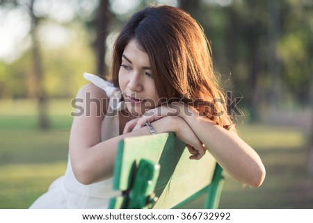 Young girl in white dress sitting on bench in park - stock photo