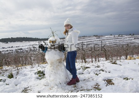 Young girl in white hat and glasses with snowman in winter field - stock photo