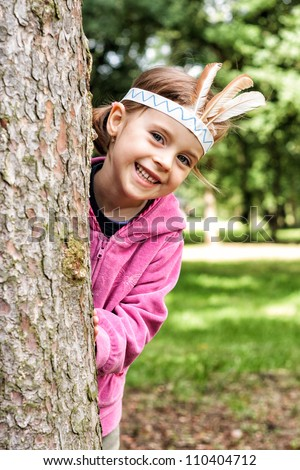Young girl indian and looking behind the tree - stock photo