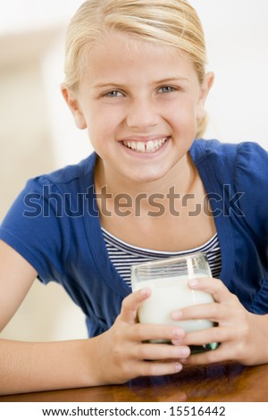 Young girl indoors drinking milk smiling - stock photo
