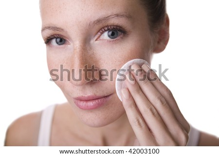 Young girl is cleaning her face cotton pad. - stock photo