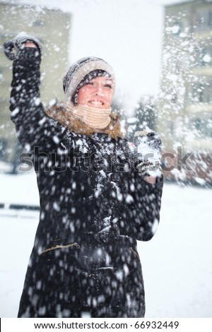 Young girl is defending herself playing snowball fight - stock photo
