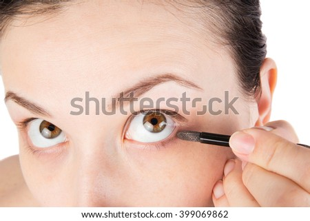 Young girl is doing her makeup, isolated on white