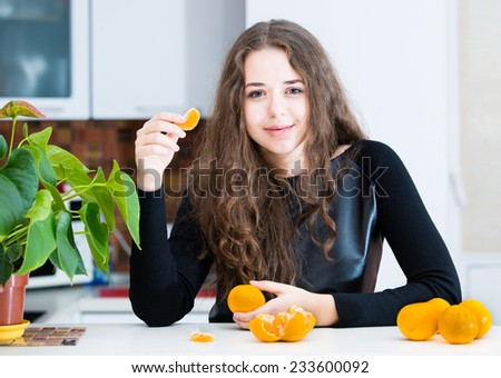 Young girl is eating an orange - stock photo
