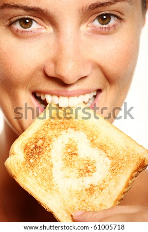 Young girl is eating fresh toast with heart shape on it