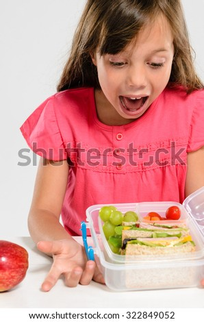 Young girl is excited about her healthy packed lunch with wholemeal ham sandwich and fresh fruit - stock photo