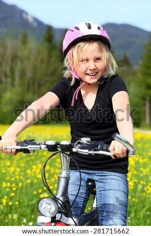young girl is going by bike in nature