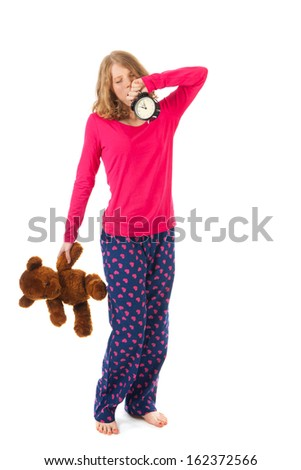 Young girl is going to bed with toy bear and alarm clock - stock photo