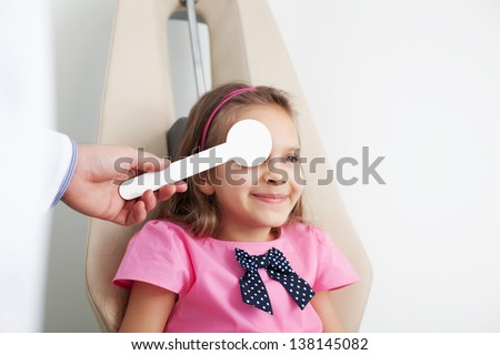 Young girl is having eye exam performed by optician, optometrist or eye doctor. - stock photo