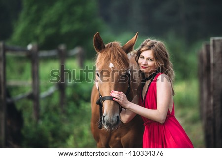 young girl is in a beautiful place and playing with horse