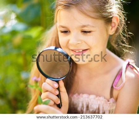 Young girl is looking at flower through magnifier, outdoor shoot - stock photo