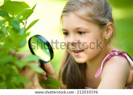 Young girl is looking at tree leaves through magnifier, outdoor shoot - stock photo