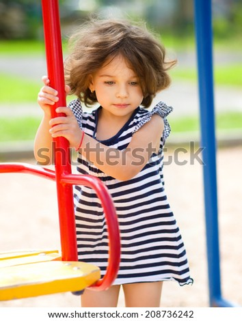Young girl is playing in playground, outdoor shoot - stock photo