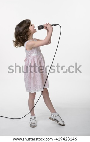 Young girl is recording her song in the studio. Singing little cutie holds black microphone in her hands on the same level with her opened mouth. Face in profile. White background in the studio. - stock photo