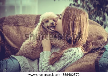 Young girl  is resting with a dog on the armchair at home . - stock photo