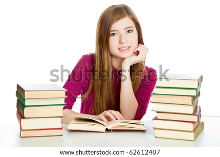 Young girl is sitting at the desk and reading the book. Isolated on white background - stock photo