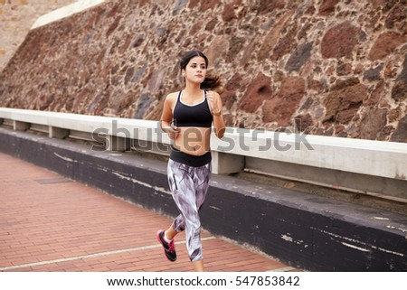 Young girl jogging on a paved road next to a rock wall barrier, wearing casual clothes, running shoes and her hair tied back