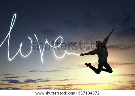 Young girl jumping high in sky and drawing love word