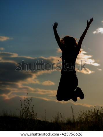 young girl jumping in the sunset light